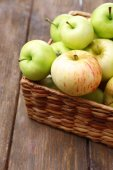 Ripe apples in basket on wooden table close-up — Stock Photo