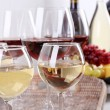 Bottles and glasses of wine, cheese and ripe grapes on table in room — Stock Photo #51912451