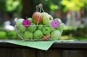 Ripe apples in basket outdoors — Stockfoto
