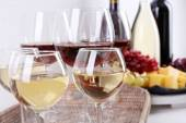 Bottles and glasses of wine, cheese and ripe grapes on table in room — Stock Photo