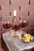Bottle and glasses of wine and cheese on table on brick wall background — Stock Photo