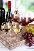 Bottles and glasses of wine and ripe grapes on table on natural background — Stock Photo