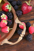 Different berries and fruits on tray on wooden table close-up — Foto Stock