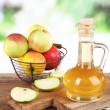 Apple cider vinegar in glass bottle and ripe fresh apples, on wooden table, on nature background — Stock Photo #52099787