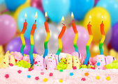 Birthday cake with candles on bright background — Stock Photo
