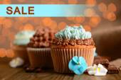 Concept of discount. Tasty cupcakes with butter cream on lights background — Stock Photo