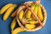 Bunch of mini bananas in wicker basket on color wooden background — Stock Photo