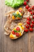 Tasty bruschetta with tomatoes, on old wooden table — Stock Photo