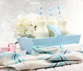 Milk in bottles with paper straws on table — Stockfoto