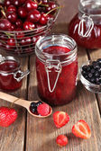 Berries jam in glass jar on table, close-up — Stockfoto