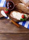 Fresh toast with homemade butter and strawberry jam on wooden background — Stockfoto