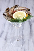Martini glass of fresh tasty prawns with lemon and dill on grey wooden background — Stockfoto