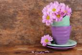Cups and saucers with flowers on wooden background — Stock Photo