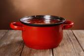 Cooking pot with steam on table on brown background — Stock Photo
