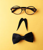 Glasses, mustache and bow tie forming man face on yellow background — Photo