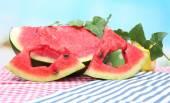 świeże plasterki arbuza na stole, na niebieskim tle — Zdjęcie stockowe