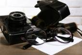Retro camera on table with glasses and sheets of paper — Stock Photo