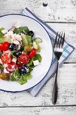 Plate of Greek salad served on napkin on wooden background — Zdjęcie stockowe