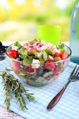 Glass bowl of Greek salad served with water on napkin on wooden table on natural background — Stock Photo