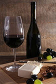 Beautiful still life with wine, cheese and ripe grape on wooden background — Stok fotoğraf
