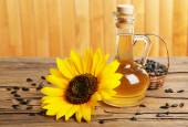 Sunflower with seeds and oil on wooden background — Stock Photo