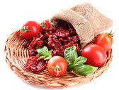Getrockneten Tomaten, frische Tomaten auf Wicker Mat, Basilikumblätter, isoliert auf weiss — Stockfoto