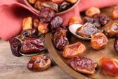 Tasty dates fruits on old metal tray, on wooden background — Zdjęcie stockowe