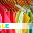 Concept of discount. Colorful clothes on hangers in wardrobe — Stock Photo #52142135