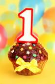Birthday cupcake with chocolate frosting on bright background — Stock Photo
