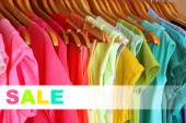 Concept of discount. Colorful clothes on hangers in wardrobe — Stock Photo