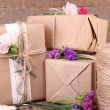 Beautiful gifts with flowers and decorative rope, on old wooden background — Fotografia Stock  #52323559