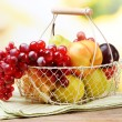 Assortment of juicy fruits in wicker basket on table, on bright background — Stock Photo #52324565