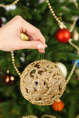 Christmas ball in hand on Christmas tree background — Stock Photo