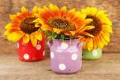 Beautiful sunflowers in cans on table on wooden background — Stock Photo