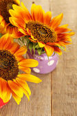 Beautiful sunflowers in cans on wooden background — Stock Photo