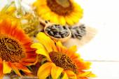Sunflowers with oil and seeds on wooden background — Stock Photo