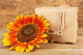 Sunflowers with present box on wooden background — Stock Photo