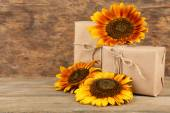 Sunflowers with present boxes on wooden background — Stock Photo