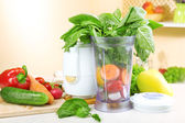 Blender with fresh vegetables on kitchen table — Stock Photo