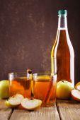 Bottle of apple vinegar with fresh apples on wooden table — Stock Photo