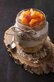 Petit-déjeuner sain - yogourt aux pêches fraîches et muesli, servi en pot de verre, sur fond de bois — Photo