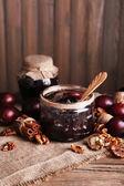Chutná povidla ve sklenicích a švestky na dřevěný stůl na dřevěné pozadí — Stock fotografie