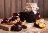 Tasty plum jam in jar and plums on wooden table close-up — Stock Photo