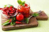 Sun dried tomatoes in glass jar, basil leaves on cutting board, on table background — Stock Photo