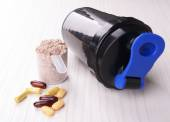 Whey protein powder in scoop with vitamins and plastic shaker on wooden background — Stock Photo