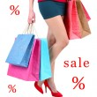 Concept of discount. Female in red shoes holding shopping bags isolated on white — Stock Photo #52335603