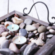 Candles on vintage tray with sea pebbles, on wooden background — Stock Photo #52337573