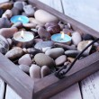 Candles on vintage tray with sea pebbles, on wooden background — Stock Photo #52337579