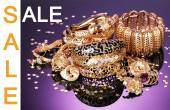 Concept of discount. Beautiful golden jewelry on purple background — Stock Photo