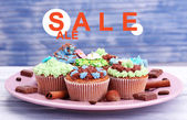 Concept of discount. Tasty cupcakes with butter cream, on plate, on color wooden background — ストック写真